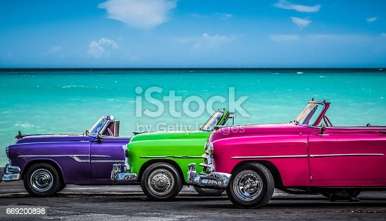 HDR - Three american colorfully convertible vintage cars parked before the caribbean sea on the Malecon in Havana Cuba  - Serie Cuba Reportage