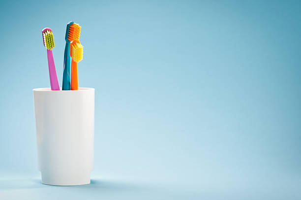 Three colourful soft toothbrushes in white mug on blue background stock photo