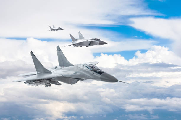 Three combat fighter jet on a military mission with weapons - rockets, bombs, weapons on wings flies high in the sky above the clouds. Three combat fighter jet on a military mission with weapons - rockets, bombs, weapons on wings flies high in the sky above the clouds fighter plane stock pictures, royalty-free photos & images