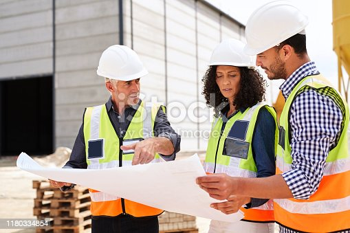 Three diverse construction engineers wearing hardhats and safety vests standing on a worksite going over blueprints together