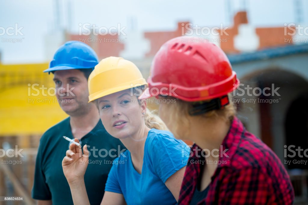 Three construction worker taking a break on construction site stock photo