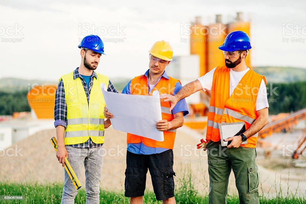 Drei Bauarbeitern und engineers auf Baustelle – Foto