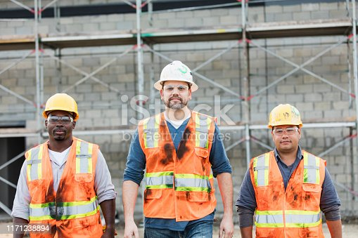 A group of three multi-ethnic construction workers wearing hard hats, safety glasses and reflective vests, walking toward the camera with serious expressions. The man on the right side is Hispanic, in his 20s. The one on the left is African-American, in his 30s.  An the one in the middle is in his 40s.