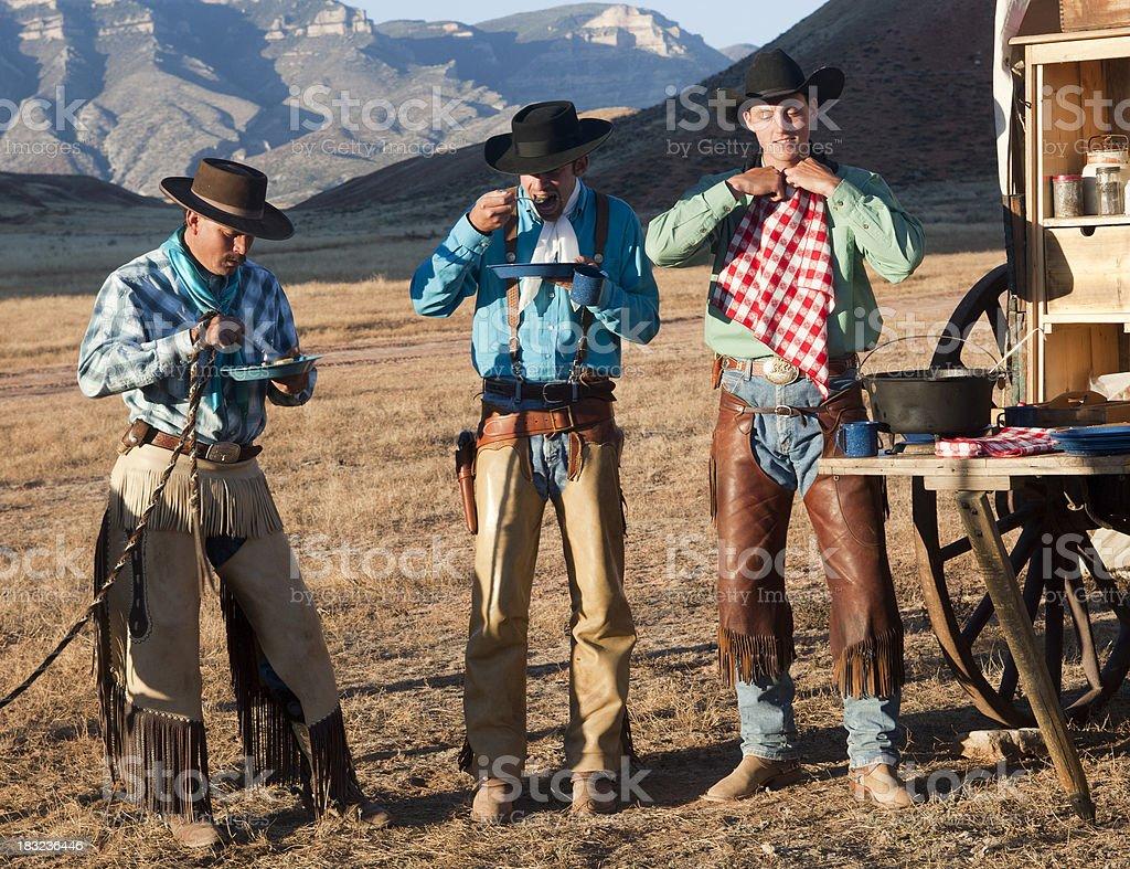 Three cowboys have meal at chuckwagon in Wyoming stock photo