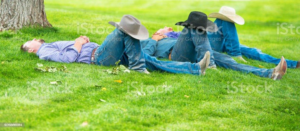 Three Cowboys Sleeping Under A Shade Tree Hats On Knees royalty-free stock  photo 2894e4a42fd