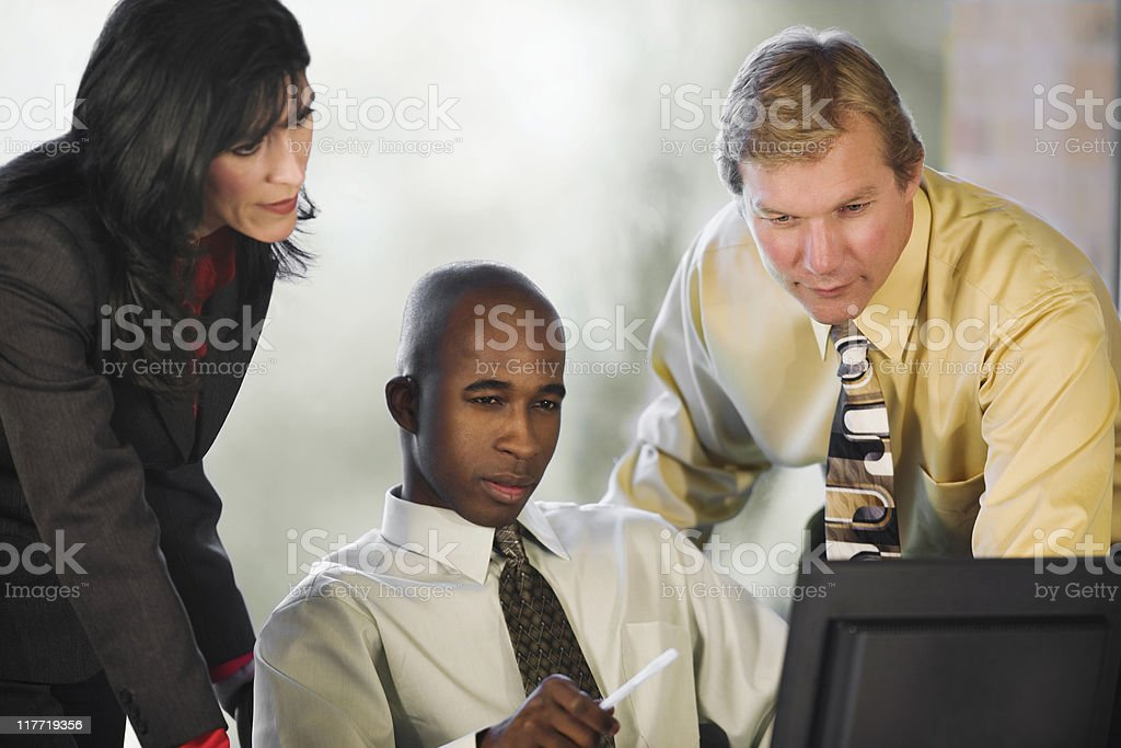 Three Co-Workers Looking At Computer royalty-free stock photo