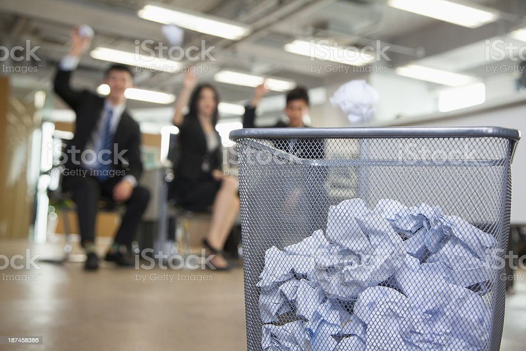 Three coworkers preparing to throw paper into waste basket stock photo