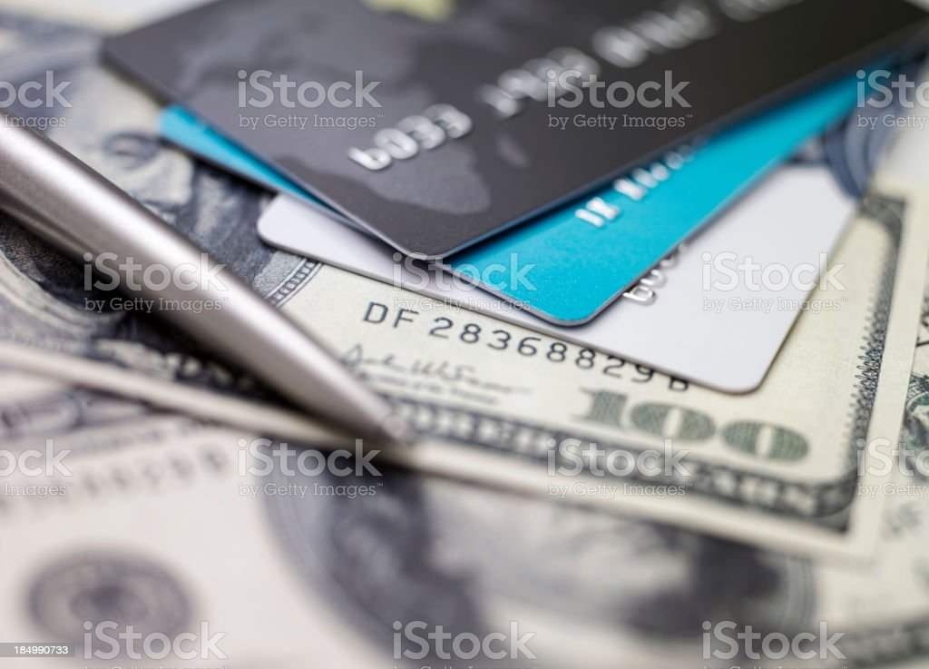 Three credit cards piled on top of dollar bills stock photo