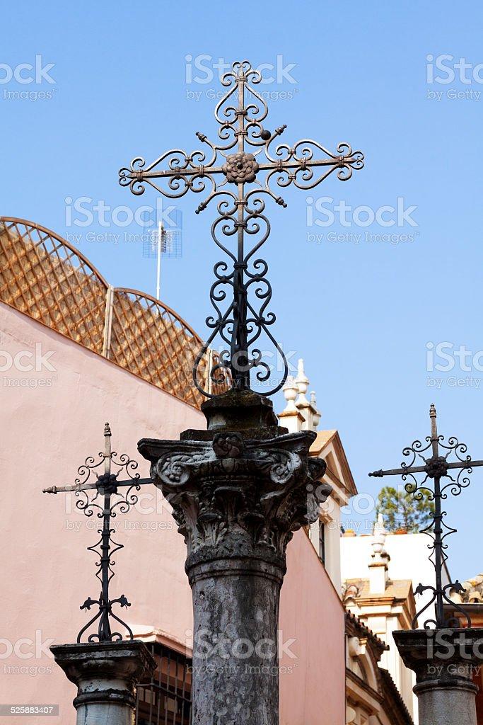 Old three crosses on columns at square Plaza de Santa Cruz in Sevilla.