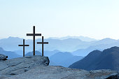 Three crosses on a cliff at sunrise symbolize the Crucifixion of Christ  as the sun rises in the distance.  A series of mountain ridges disappear into the horizon