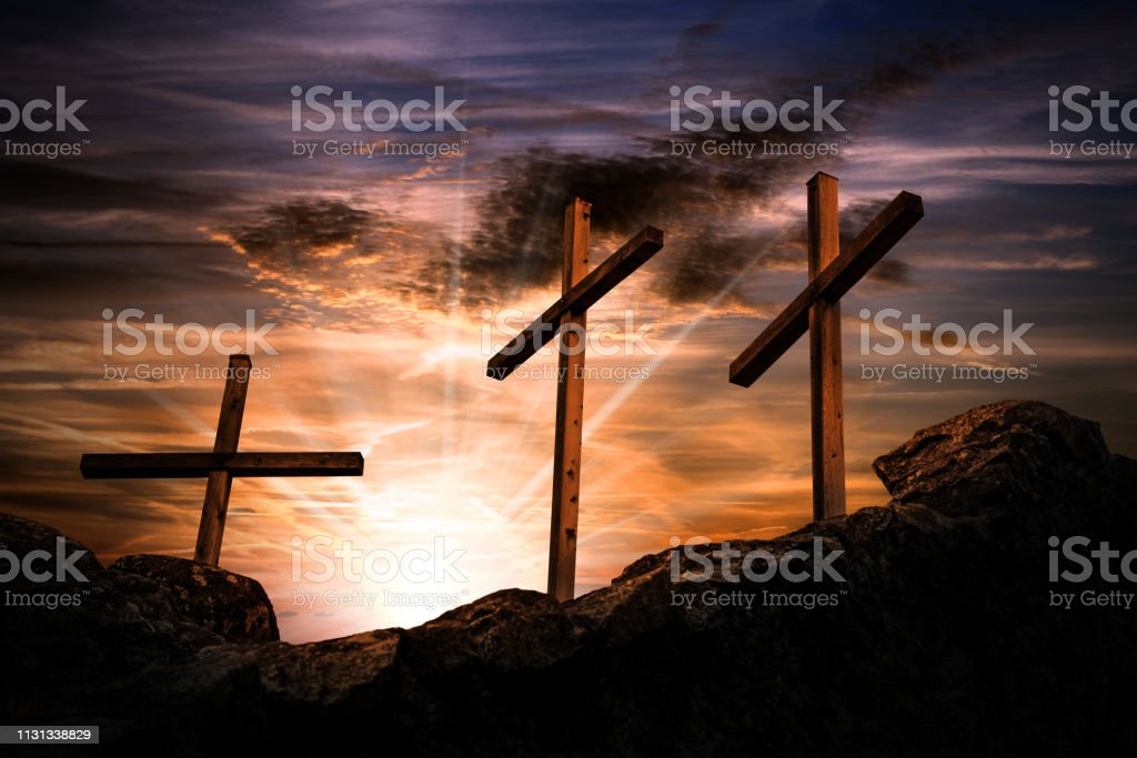 Silhouette of three wooden crosses above the hill with dramatic sky...