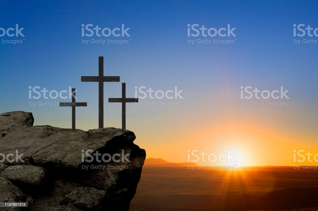 Three crosses sit on a rocky butte as they are silhouetted against a...