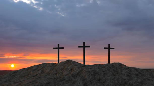 tres cruces en la cima de una colina al atardecer - foto de stock