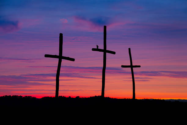 Three crosses silhouetted against sunset sky stock photo