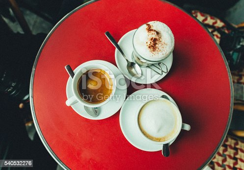 3 cups of hot latte, espresso, capuccino coffees with  spoon on red color wooden table in a cafe restaurant