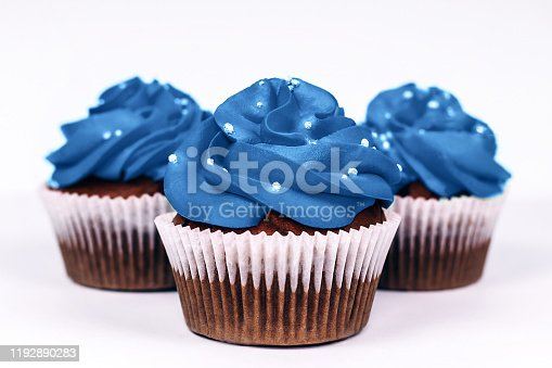 Three delicious cupcakes with icing in trendy blue color on isolated white background. Color of the year 2020 concept. Close-up.