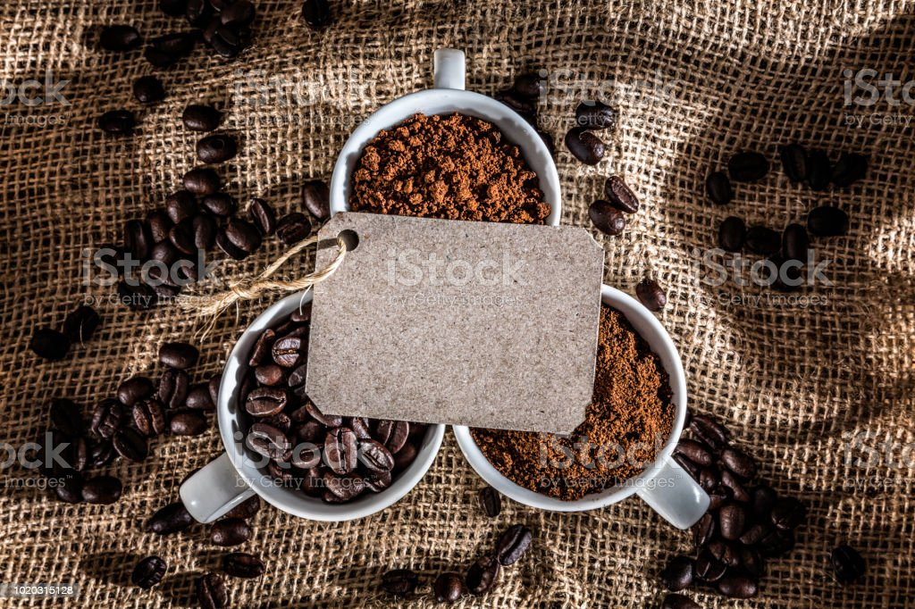 Three cups coffee beans, instant coffee and grinded coffee in jute frame with blank label for copy space stock photo