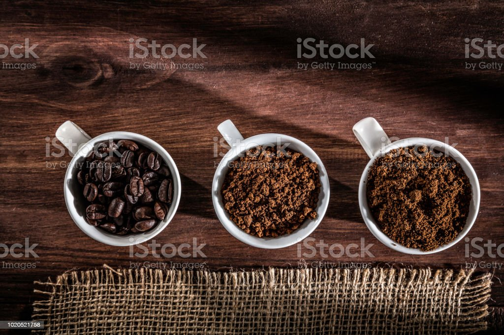 Three cups coffee beans, instant coffee and grinded coffee in jute frame stock photo