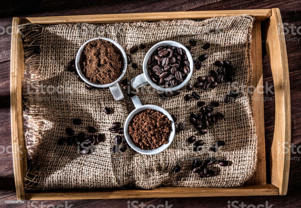 Three cups coffee beans, instant coffee and grinded coffee in wooden tray with jute stock photo