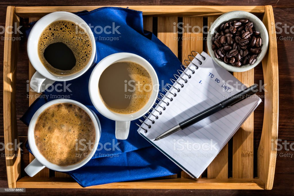 Three cups with Espresso, Cappuccino and Macchiato coffee with roasted raw coffee beans in wooden tray with note pad and to do list stock photo
