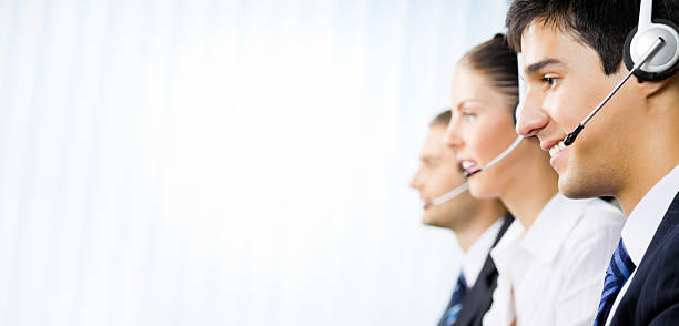Three customer support phone operators at office stock photo