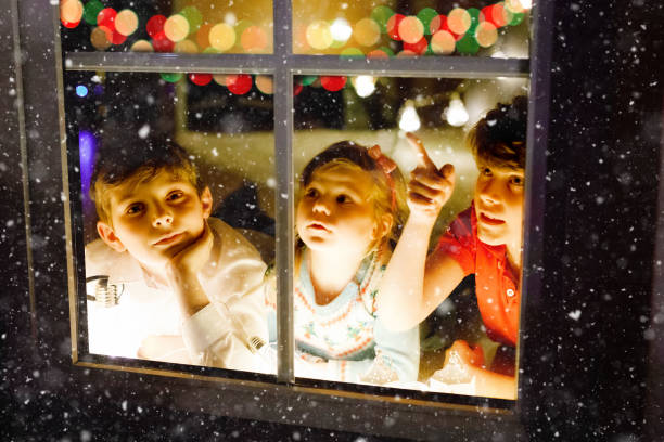 Three cute children sitting by window on Christmas eve. Two school kid boys and toddler girl, siblings looking outdoor and dreaming. Family happiness on traditional holiday stock photo