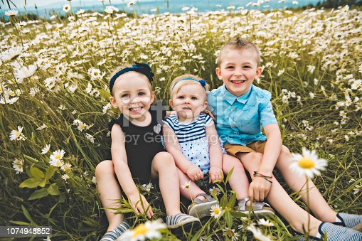istock three cute childs playing in green daisy field 1074948852