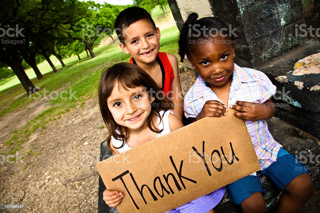 Three Cute Kids Smiling and Holding a Thank You Sign royalty-free stock photo
