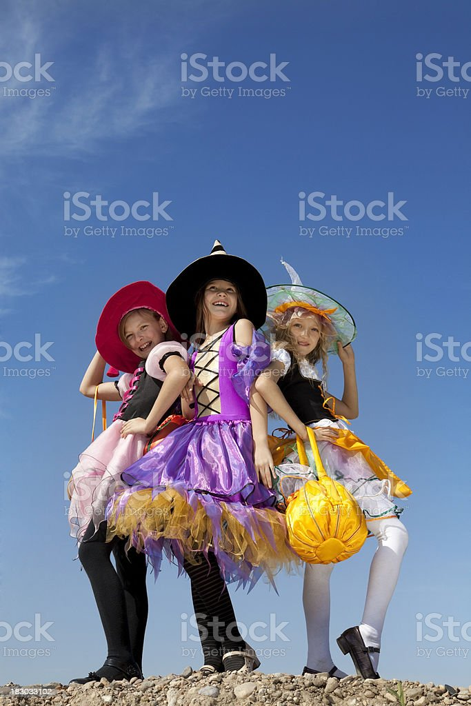 Three Cute Little Witches Standing with Bags. royalty-free stock photo