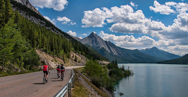 Three Cyclists On Road With Mountains stock photo