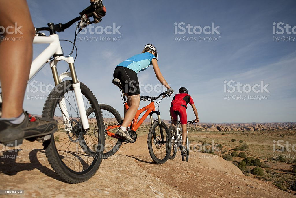 Three Cyclists Riding Mountain Bikes On Slickrock Trail royalty-free stock photo