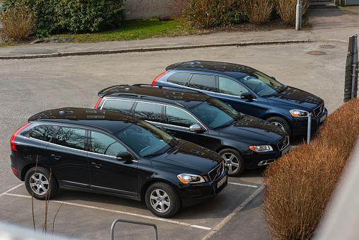 Three dark Volvo estates in row at a parking lot