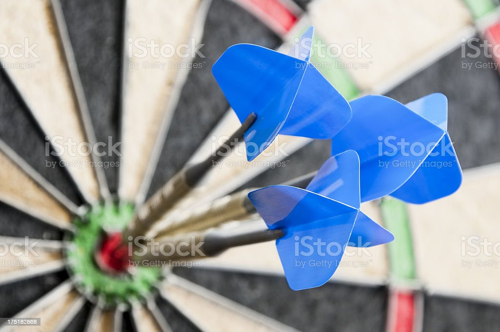 Three darts in the bulls eye on a dart board royalty-free stock photo