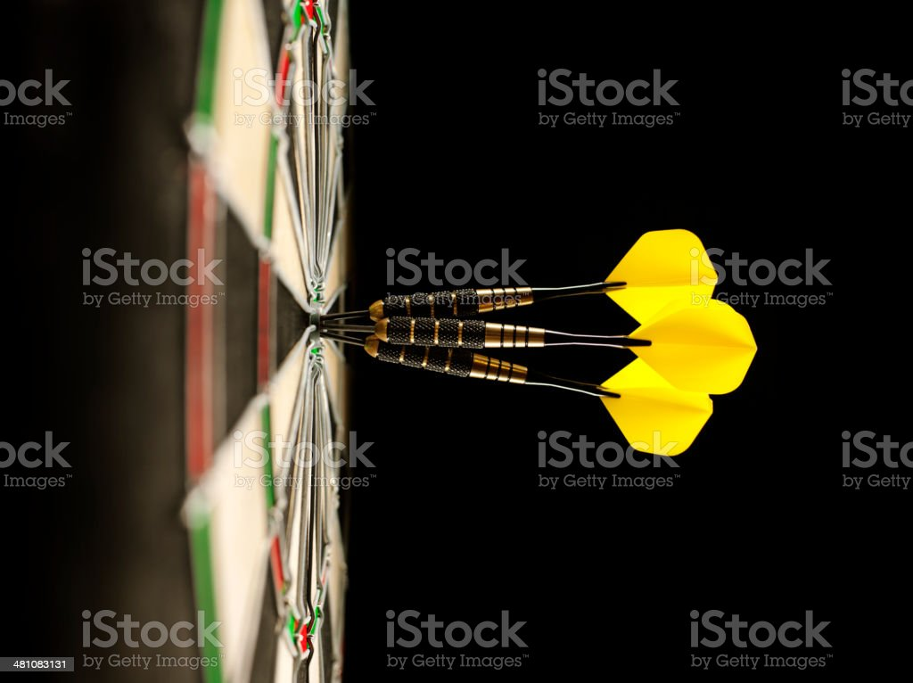 Three Darts Scoring a Bull's Eye in a Dartboard stock photo