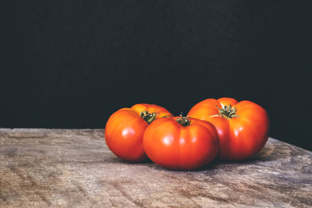 Three delicious fresh tomatoes on a rustic wooden table with black background stock photo