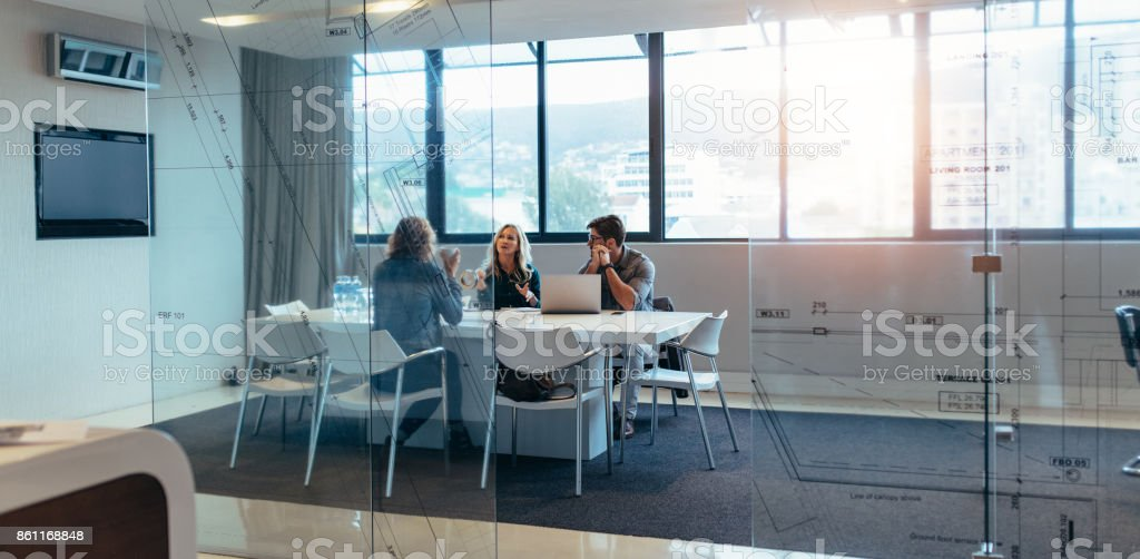 Three designers discussing in meeting hall stock photo
