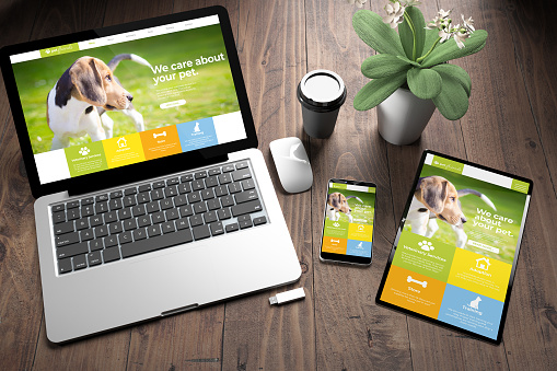 istock three devices on wooden desk top view pet website 1157335300