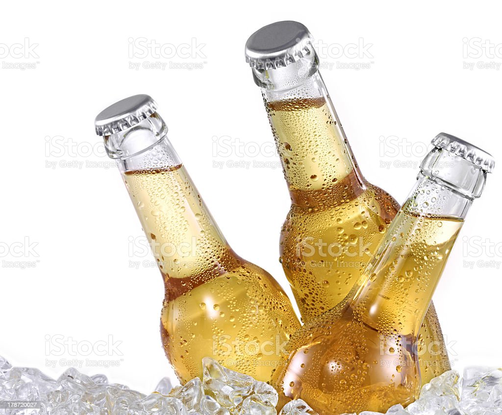 Three dewy beer bottles on ice stock photo