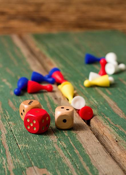 Three dices and color figurines on old wooden board stock photo