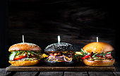 three different burgers in a line on a wooden Board on a dark background