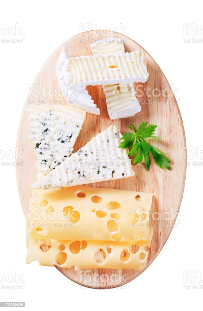 Three different cheeses displayed on a wooden cutting board royalty-free stock photo