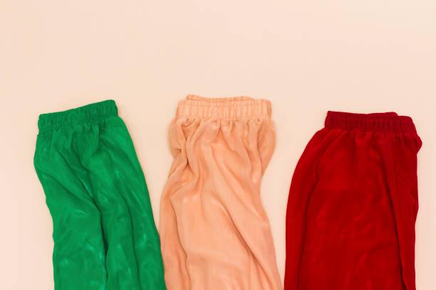 drei verschiedene farbe grün, garnelen, rot chiffon maxi rock auf rosa hintergrund isoliert - spitzen maxi stock-fotos und bilder