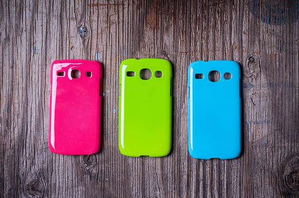 Three different colored cell phone covers on wooden table stock photo