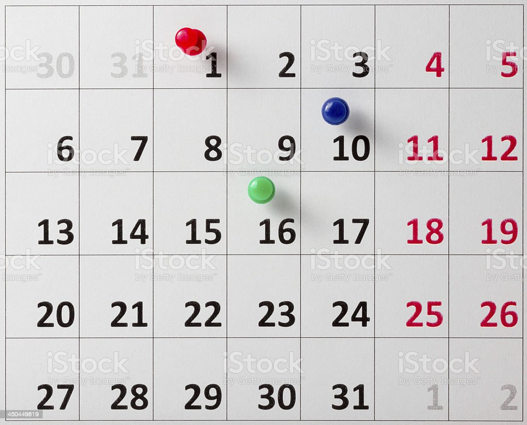 Three different colored push pins stuck on calendar royalty-free stock photo
