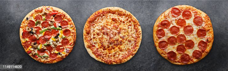 three different pizzas in panoramic composition on dark surface
