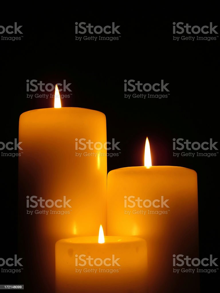 Three different size lit candles against a black background royalty-free stock photo