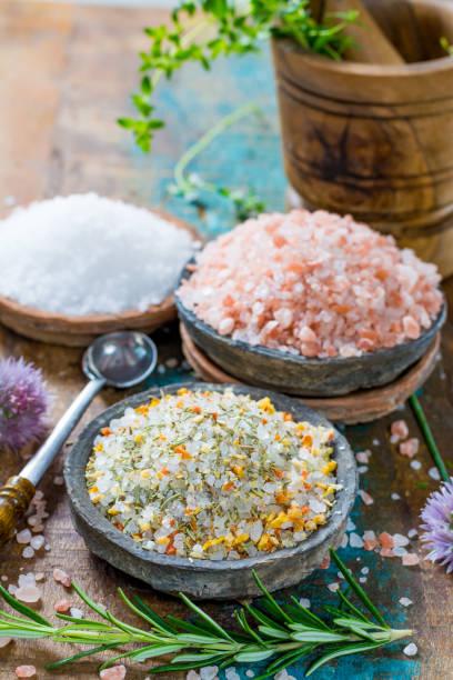drei verschiedene arten von natursalz in stein schalen auf der holzoberfläche. weißes meer salz, rosa himalaya salz, salz gewürzt mit rosmarin - pyramide sammlung stock-fotos und bilder