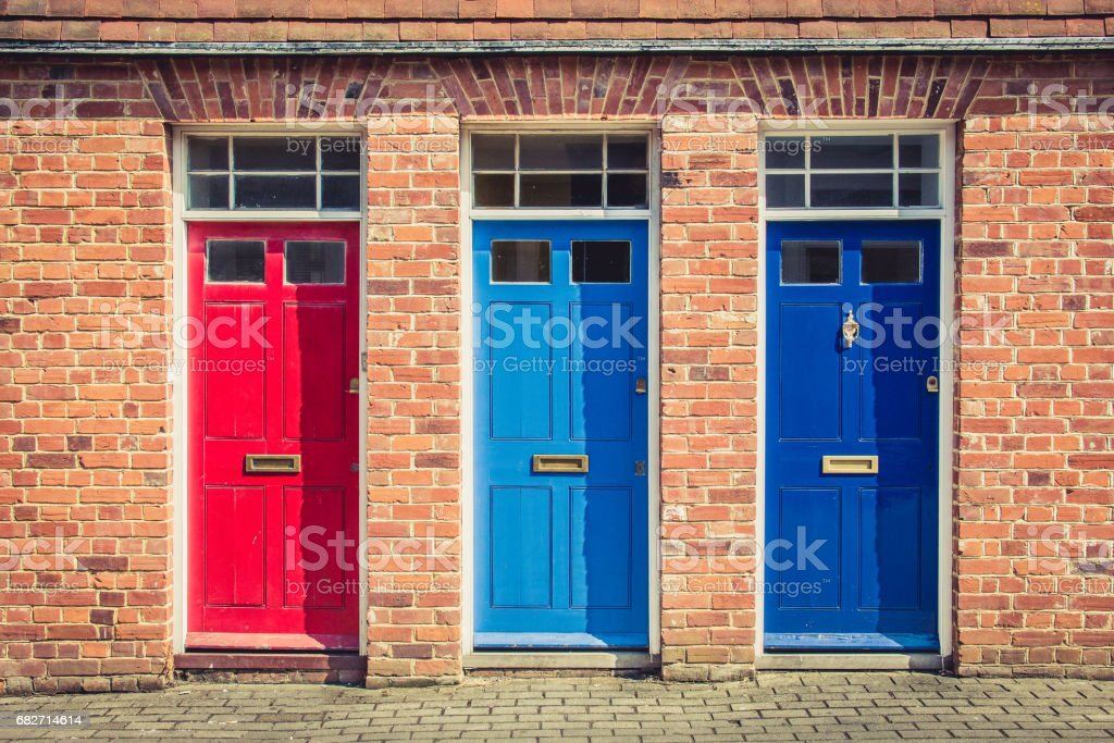 Three differently coloured front doors at the entrance of old English terraced houses. Canterbury, England. stock photo