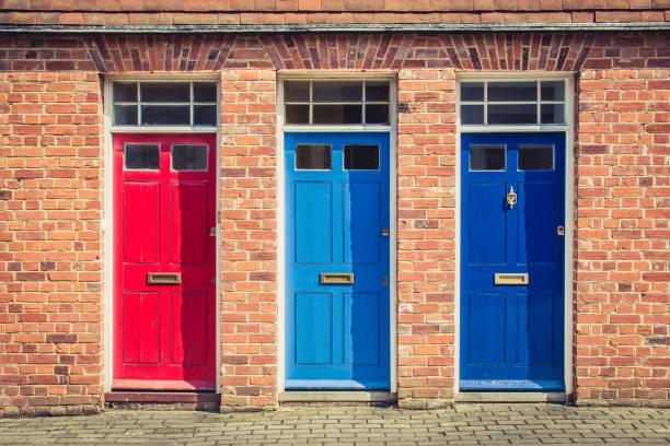 drei verschiedenfarbige haustüren am eingang alter englischer reihenhäuser. canterbury, england. - paletten terrasse stock-fotos und bilder