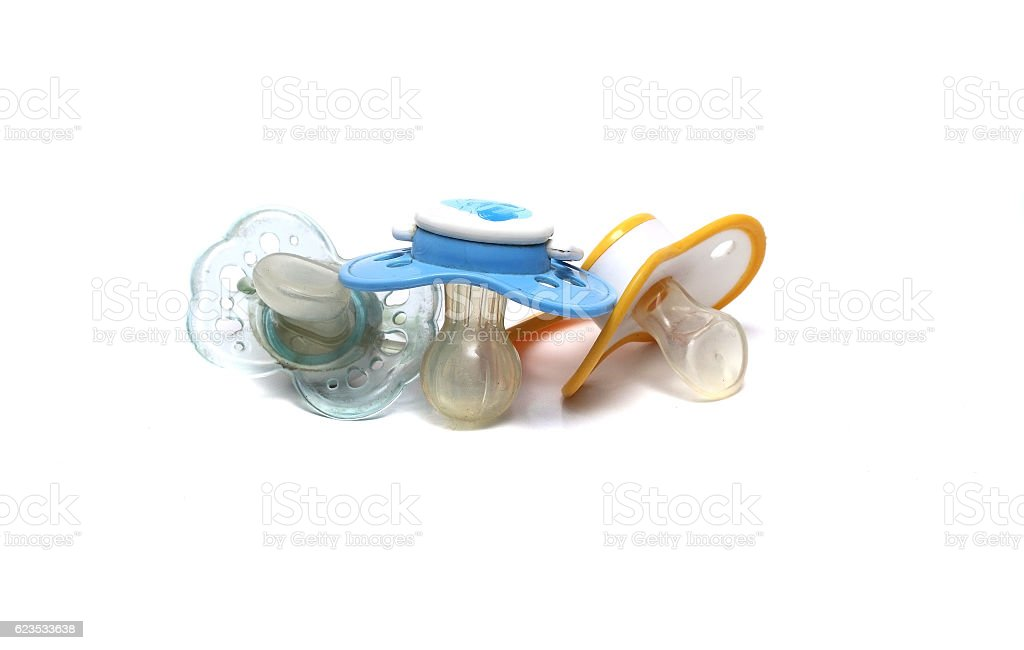 three dirty pacifiers on a white background stock photo
